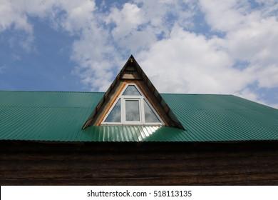 Triangular skylight of an attic of a village log house under construction against a cloudy sky
