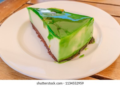 Triangular slice of green glazed soft flan cake on a brown biscuit base served on a white round plate on a woode table