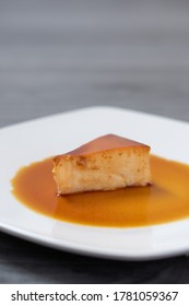 triangular slice of a Neapolitan custard on a white plate lying on a light gray wooden table
