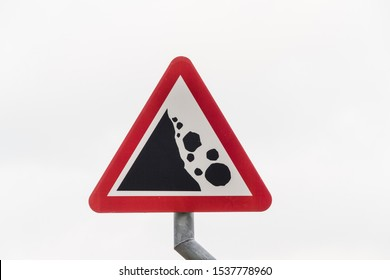 Triangular UK warning or hazard sign for Falling or fallen rocks, landscape.