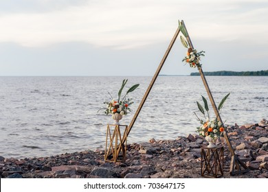 Triangular wedding arch in boho style in the coast of sea.