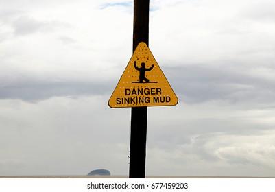 Triangular yellow sign saying danger sinking mud on an English beach at Weston Super Mare, Somerset