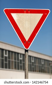 Triangular yield traffic sign outside an urban building