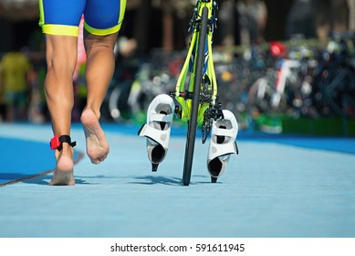 Triathlete running with your bike the transition zone,detail of the legs
