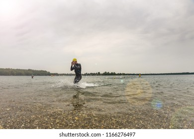 A triathlete in a wetsuit runs out of the water