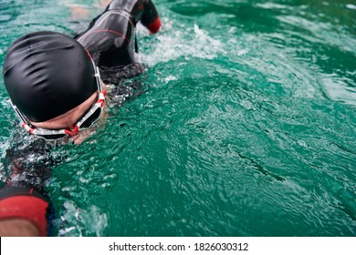 triathlon athlete swimming on lake wearing wetsuit