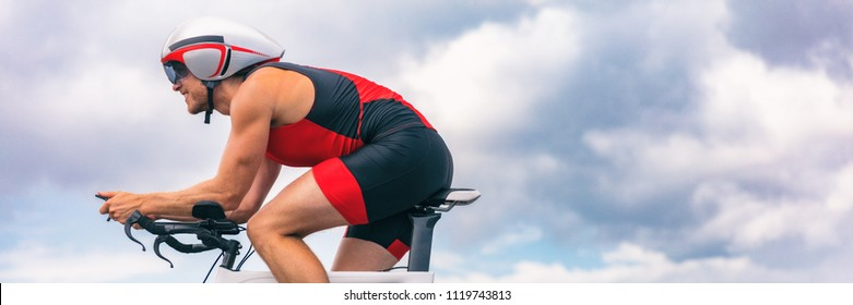 Triathlon biking man cycling on road bike with time trial helmet. Panorama banner crop for sky copy space.