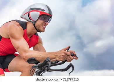 Triathlon biking man cyclist portrait riding bike. Male triathlete cycling on triathlon bike. Fit man professional athlete on triathlon bicycle wearing time trial helmet for ironman race.