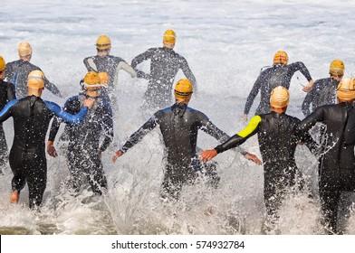 triathlon competitors in swim portion of race , selective focus