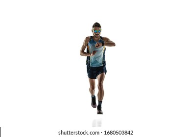 Triathlon male athlete running isolated on white studio background. Caucasian fit jogger, triathlete training wearing sports equipment. Concept of healthy lifestyle, sport, action, motion. Time check.