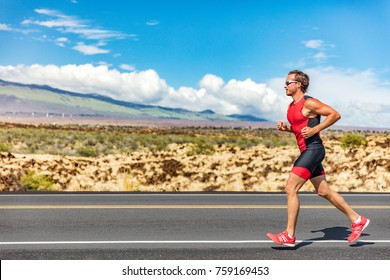Triathlon runner triathlete man running in tri suit at ironman competition race on road. Sport athlete on marathon run training exercising cardio in professional outfit for triathlon. Fitness Hawaii.