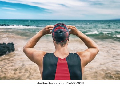 Triathlon swim sport man on race . Swimmer getting ready for open ocean competition. Triathlete from behind putting goggles.