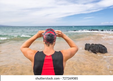 Triathlon swimmer going swimming ready to swim looking at ocean horizon. Man triathlete swimmer putting goggles for competition. Professional athlete in triathlon suit training for Hawaii ironman.