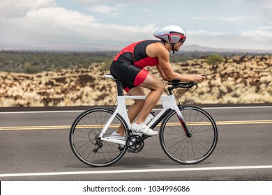 Triathon biking cyclist man triathlete riding racing bike during ironman competition. Road cycling athlete in tri suit and helmet.