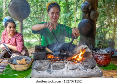 Tribal women cooking. Pan with batter for cooking a special kind of food. Mari Mari Cultural Village