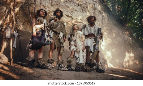 Tribe of Four Hunter-Gatherers Wearing Animal Skin Holding Stone Tipped Tools, Pose at the Entrance of their Cave. Portrait of Two Grown Male and Two Female Neanderthals and their Way of Living