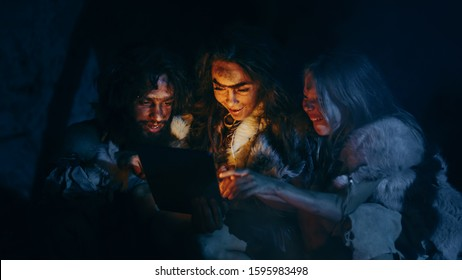 Tribe of Prehistoric, Primitive Hunter-Gatherers Wearing Animal Skins Use Digital Tablet Computer in a Cave at Night. Neanderthal or Homo Sapiens Family Browsing Internet, Watching Videos, TV Shows