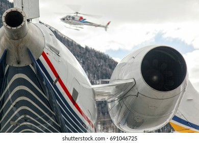 A tribune of a private jet and a flying helicopter