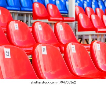Tribune of stadium. Red and blue numbered empty plastic armchairs. Seats for spectators stand in a row. Passage between tribunes