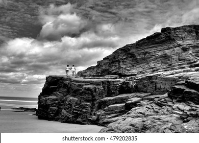 tribute to Ansel Adams, two friendly women climbing together by the cliff, allegory of friendship,series of artistic black and white photographs of the beach of the cathedrals,
