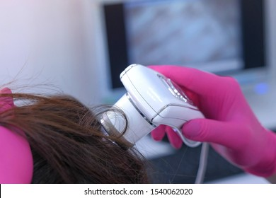 Trichologist examines woman patient's hairs using computer trichoscopy in clinic. Runs a trichoscope over head skin and looks at hairs on monitor screen, hands closeup. Diagnostic of hair follicles.