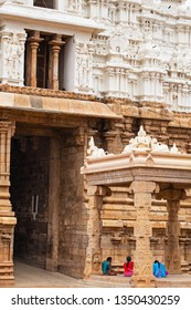 Trichy, India - March 14, 2018: Saris of pilgrims provide a contrast with the plain gateway, known as the Vellai gopuram and symbolising purity, in the Dravidian Sri Ranganatha Swamy temple complex