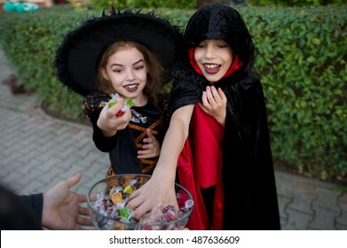 Trick or Treat. Boy and girl in black suits for Halloween take candies from a vase. On the children's faces frightening makeup. Children delighted with the event. Halloween Party.