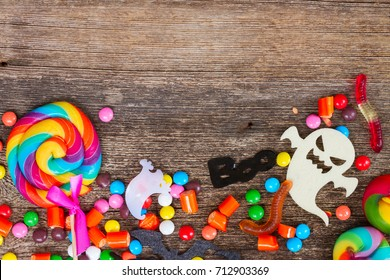 Trick and treat - colorful halloween candies border on wood