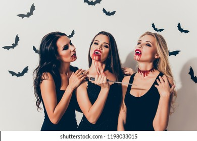 Trick or treat! Or death! Diabolic, satanic, cursed, paranormal creatures of the night. Terrifying gothic ladies with beaming white cuspids, holding weapon, willing to kill, with closed eyes, thirst