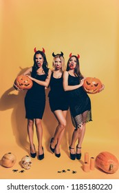 Trick or treat! Diabolic, satanic, cursed, paranormal, terrifying, gothic witches with beaming white bloody canines, cruel eyes, holding cutted squash, isolated on background with braincase, spiders