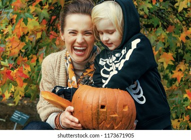Trick or Treat. happy modern mother and daughter  at the park playing with carved Halloween pumpkin