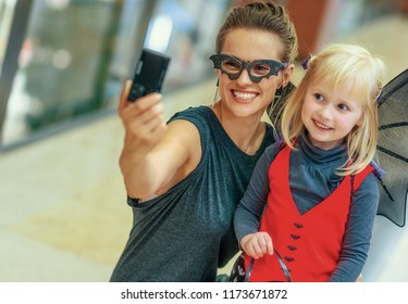 Trick or Treat. happy trendy mother and child in bat costumes on Halloween at the mall with digital camera taking selfie