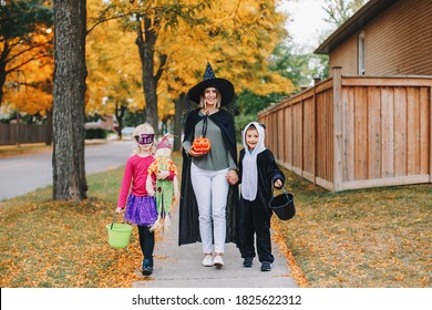 Trick or treat. Mother with children going to trick or treat on Halloween holiday. Mom with kids boy and girl in party costumes with baskets going to neighbour houses for candies and treats.