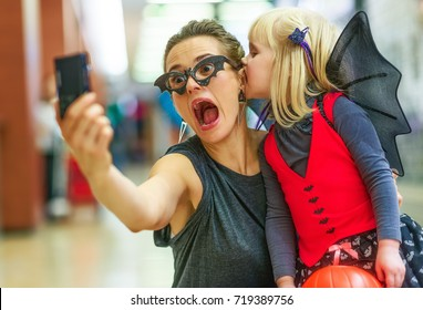 Trick or Treat. Portrait of trendy mother and daughter in bat costumes on Halloween at the mall taking scary Halloween selfie on digital photo camera