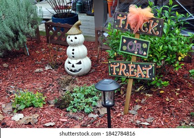 A Trick or Treat Sign in a garden bed with a ceramic pumpkin snowman.