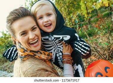 Trick or Treat. smiling modern mother and daughter on Halloween outdoors