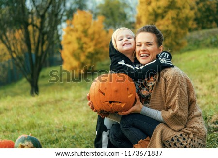 Trick or Treat. smiling modern mother and daughter on Halloween outdoors with pumpkin Jack O'Lantern