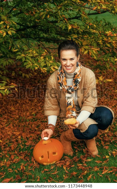 Trick or Treat. smiling young woman on Halloween outdoors putting candle in carved pumpkin