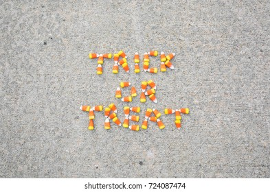 Trick or Treat spelled out in candy corn on the sidewalk.