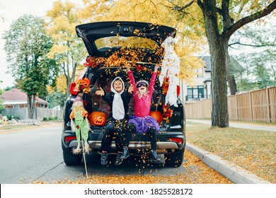 Trick or trunk. Children celebrating Halloween in trunk of car. Boy and girl with red pumpkins celebrating traditional October holiday outdoor. Social distance during coronavirus pandemic.