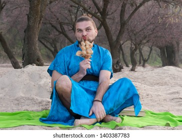 tricki transsexual handsome man with make up, hair bun sitting on sand in blue kimono, holding ship model with seashells in front of trees and looking at camera on beach