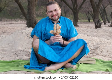 tricki transsexual handsome man with make up, hair bun sitting on sand in blue kimono, holding ship model with seashells in front of trees, looking at camera and smiling on beach