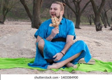 tricki transsexual handsome man sitting on sand in blue kimono, picking teeth with ship model with seashells in front of trees and looking at camera on beach