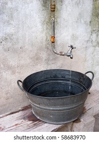 Trickle of drinkable water pouring out of a tap into an antique galvanized basin or wash tub