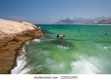 Trickliner walking on waterline in Arpoador Beach with crystal clear water and beautiful landscape of mountains on the back on a sunny day, Rio de Janeiro, Brazil
