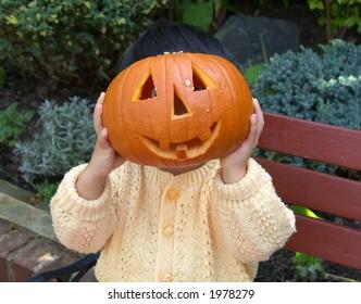 Trick-or-treat! Girl holding Halloween pumpkin