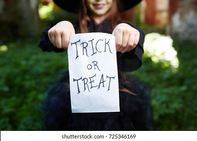 Trick-or-treat paper sack held by halloween girl in traditional attire
