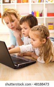 Tricks of the trade - kids learning computer usage with their mom laying on the loor