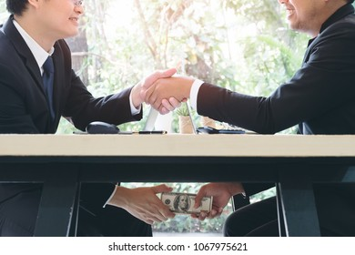 Tricky businessman shaking hand to make agreement and taking bribe corruption under table. Entrepreneur passing cash money under table to his corrupted partner. Business bribery corruption concept.