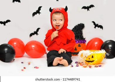 Tricky cute boy in devil costume, sitting on a background of scenery for Halloween and eating red lollipop.